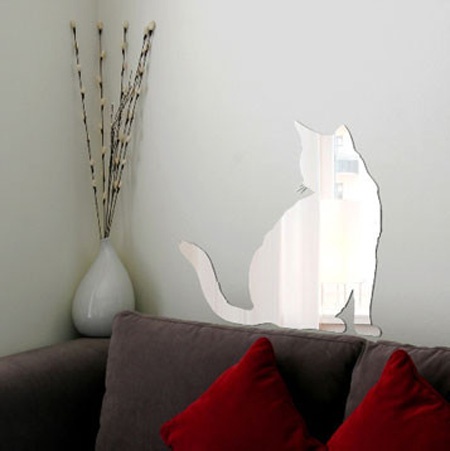 cat mirror sticker on the wall above a sofa