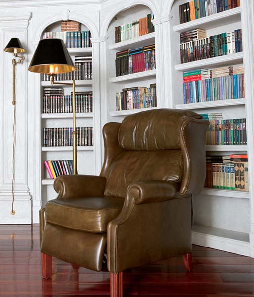 leather chair and white bookcases in home office