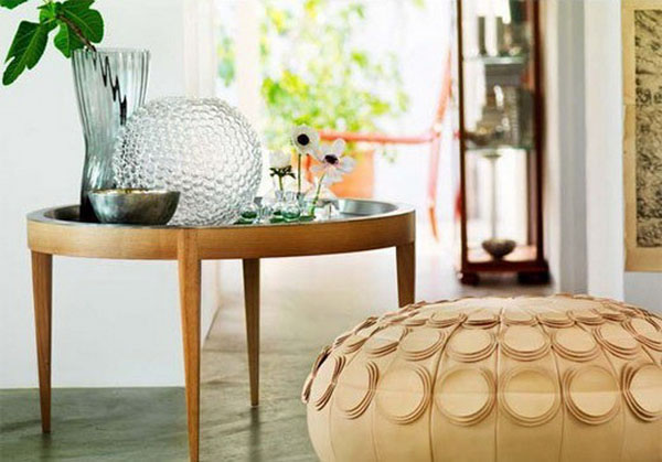 round pouf and side table with vases