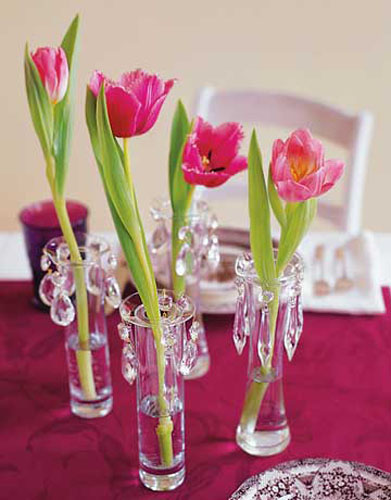 red tulips in small vases with crystals