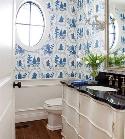 white and blue bathroom wallpaper and sconces in vintage style