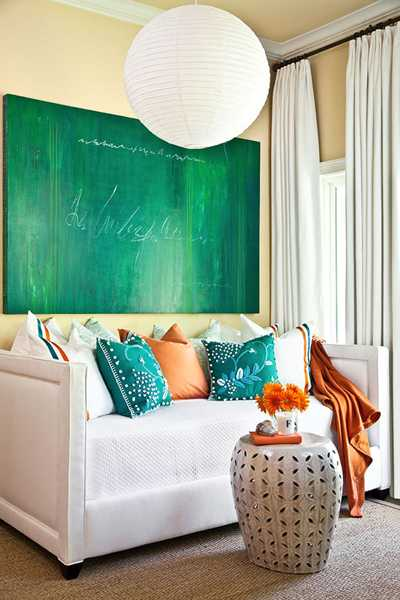 Green Paint And Cushions In Orange Blue Colors On White Sofa