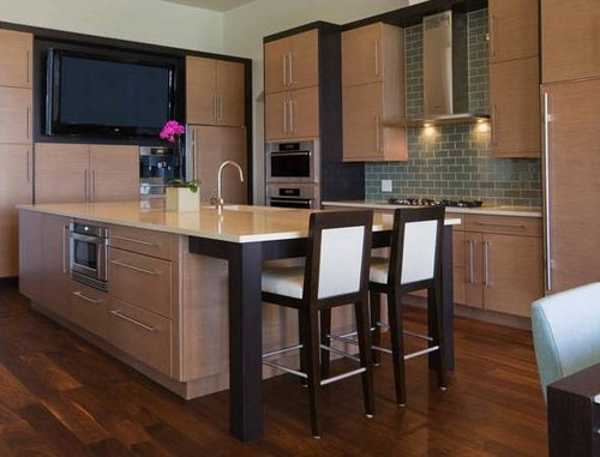 Large Kitchen Island With Dining Area And Conveniently Placed TV Set