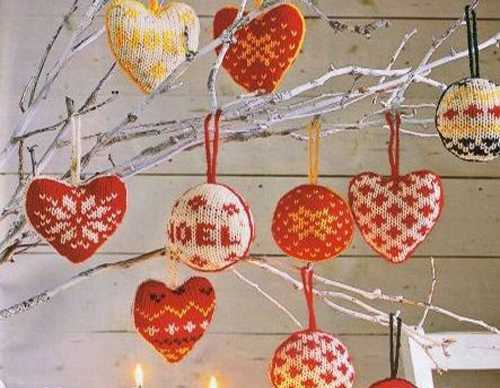 knitted christmas balls and hearts decorations in white and red colors