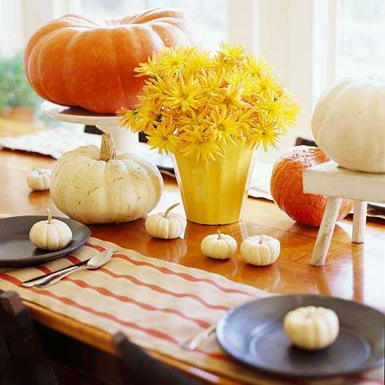 striped place mats in neutral color, pumpkins and yellow flower table centerpiece for thanksgiving decorating