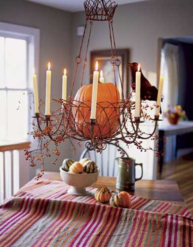 pumpkin chandelier centerpiece and thanksgiving table decorating with striped tablecloth and candles
