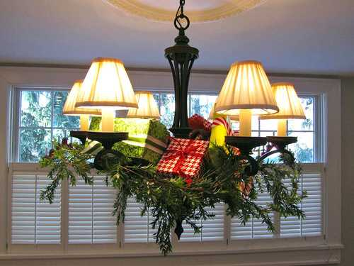 chandelier decoration with green branches and gift boxes