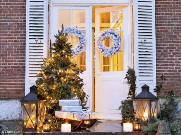 front door decoration for christmas with lanterns, christmas lights and wreaths
