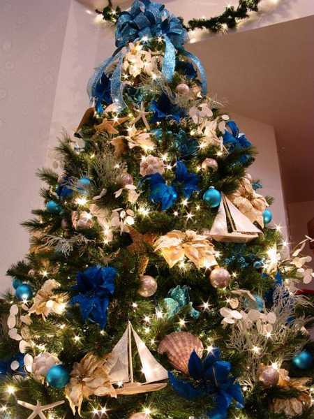 golden decorations and ribbon bows in blue color seashells and winter flowers modern christmas tree decor