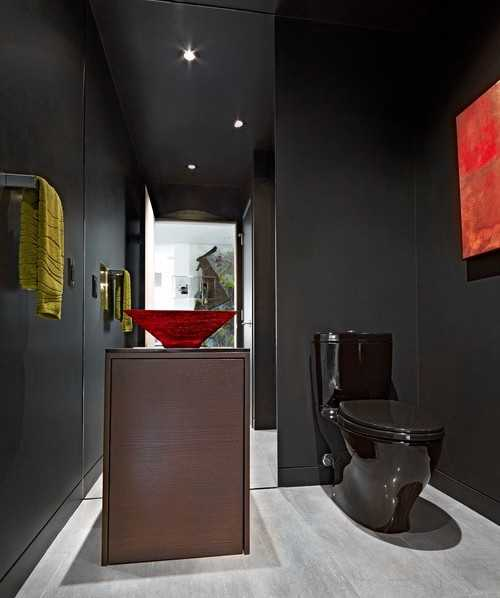 black bathroom wall and black toilet with red sink
