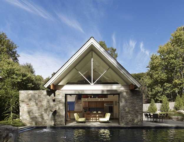 Large Pool House Design With Stone Walls And Glass Doors