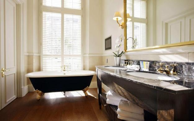 Vintage Bathroom Design With Clawfoot Bathtub And Large Wall Mirror In  Golden Frame