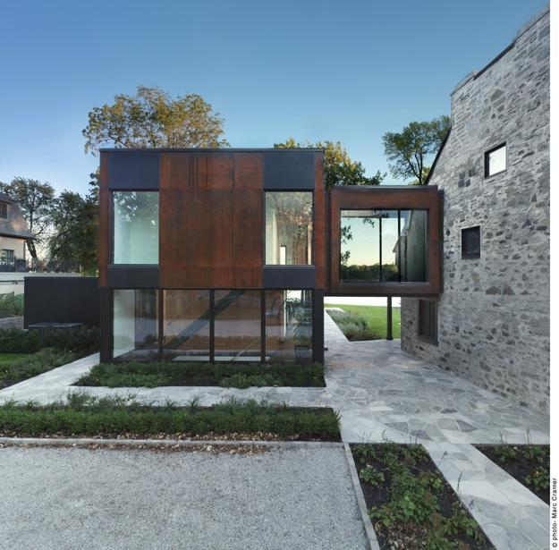 modern house addition connected to old stone wall