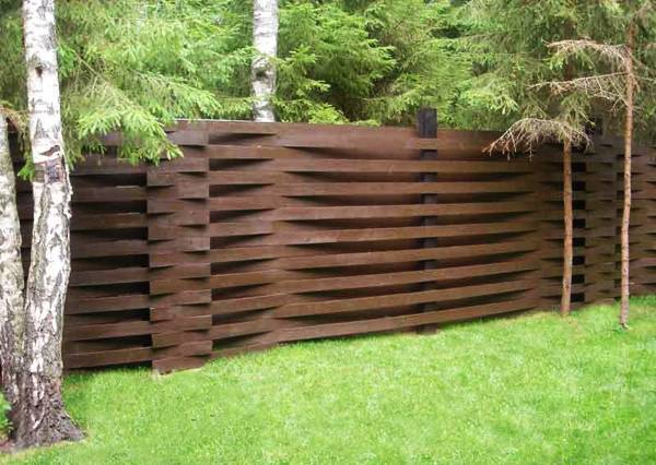 Charming wood fence along stone wall, flower beds and green grass lawns,  traditional yard landscaping ideas for sloping sites - 25 Beautiful Fence Designs To Improve And Accentuate Yard
