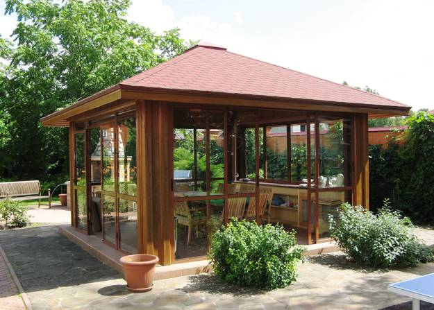 Wooden gazebo design with sliding glass doors and wooden dining furniture - 22 Beautiful Garden Design Ideas, Wooden Pergolas And Gazebos