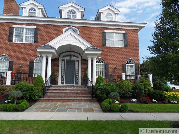 brick walls home with gray painted front door and beautiful landscaping