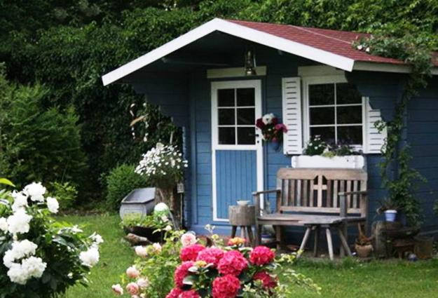 Wooden garden shed decorated with flowers in hanging baskets and wooden garden bench & Small Garden Sheds Great Outdoor Storage Solutions and Beautiful ...