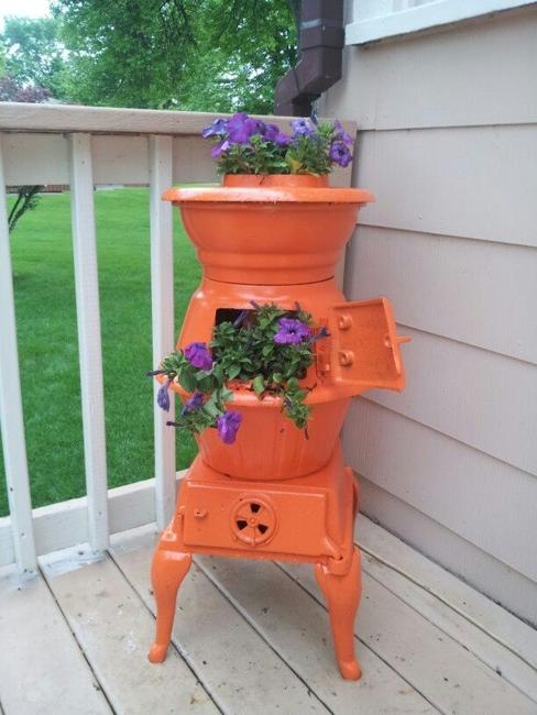 recycling old stoves for metal planters to save money on outdoor decorations