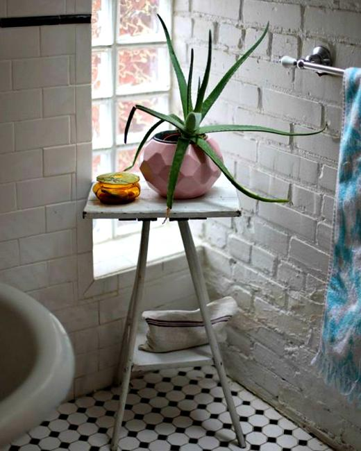 white brick wall and small side table with houseplant
