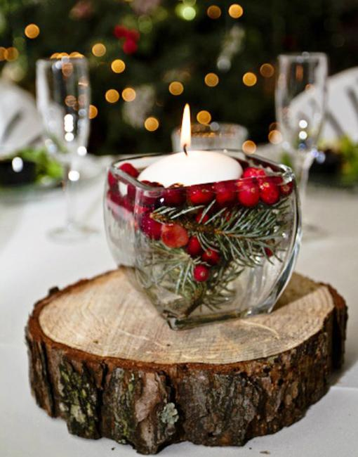 white candle and red berries table centerpiece