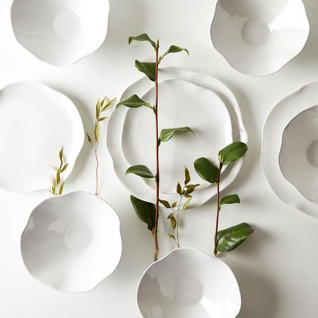 white dinnerware and green leaves for table decoration