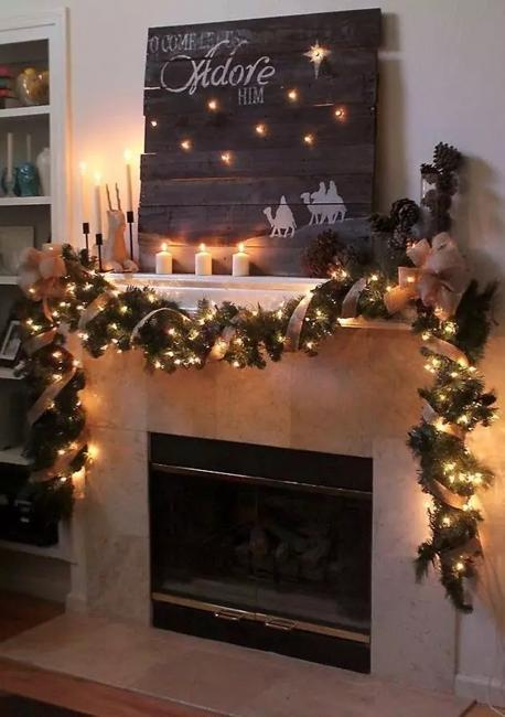 white fireplace decorated with christmas garland